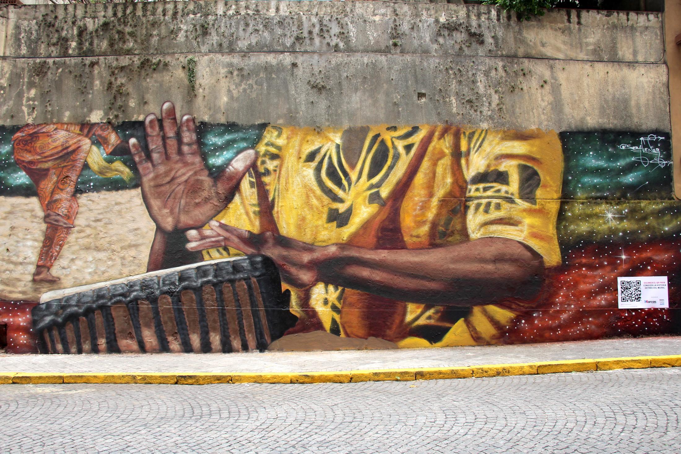 Mural manos tocando tambor y bailando